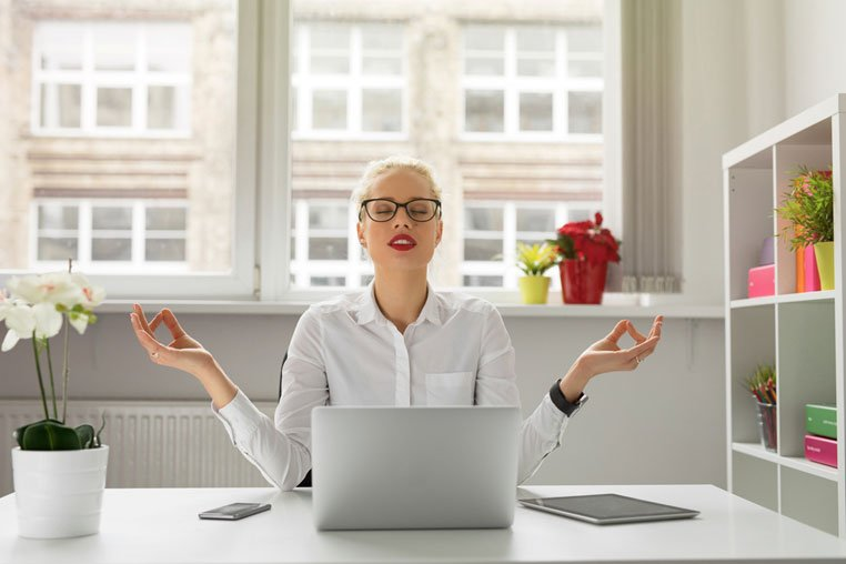 woman in home office with hands up in a meditative post