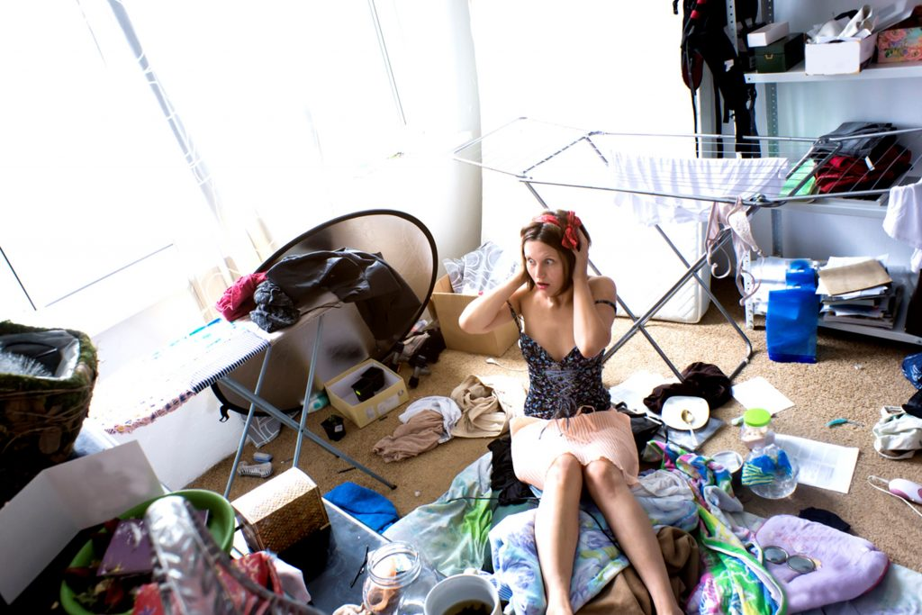 overwhelmed woman sitting in the middle of a messy room